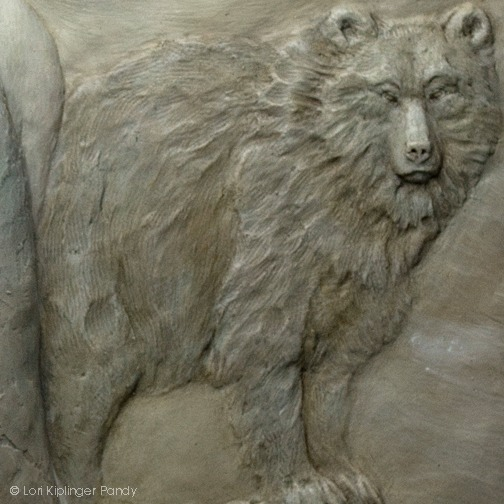 """Standing her ground"" ©Lori Kiplinger Pandy bas relief sculpture in forton of girl with bear"